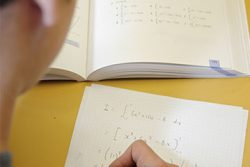 Student does maths equations in book