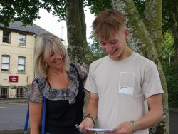 Proud parent with son collecting A Level result