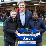 Two Sexey's students hold signed shirt with Bath Rugby player