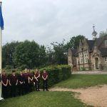 Students raising the human rights commemorative flag outside school