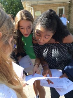 Female students congratulate each other on GCSE results