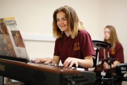 Student plays keyboard in music lesson