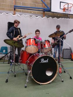 Students play drums in assembly