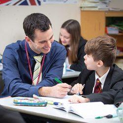 Teacher helps student with Maths work