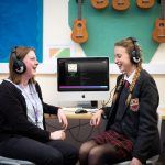 Two students laughing with the Sexey's School Playlist for Positive Mental Health in the background