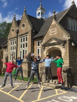 A group of male students jump for joy at GCSE results 2020