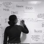Student writes 'Black: Everything and more' on a white board covered in quotes from students on what 'black' means to them