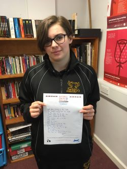 Student holds her original poem for National Poetry Day 2020