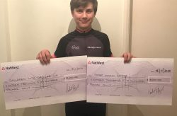Student holds two cheques made out to cancer charities for £18500 each