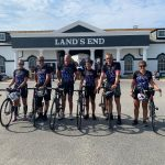 Student and fellow cyclists stand with bikes at Lands End
