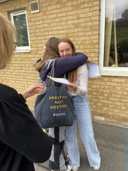 students hug on GCSE results day